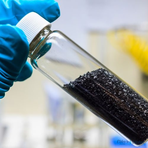 activated carbon charcoal coconut in clear bottom for use in laboratory, holding by green medical rubber hand glove.